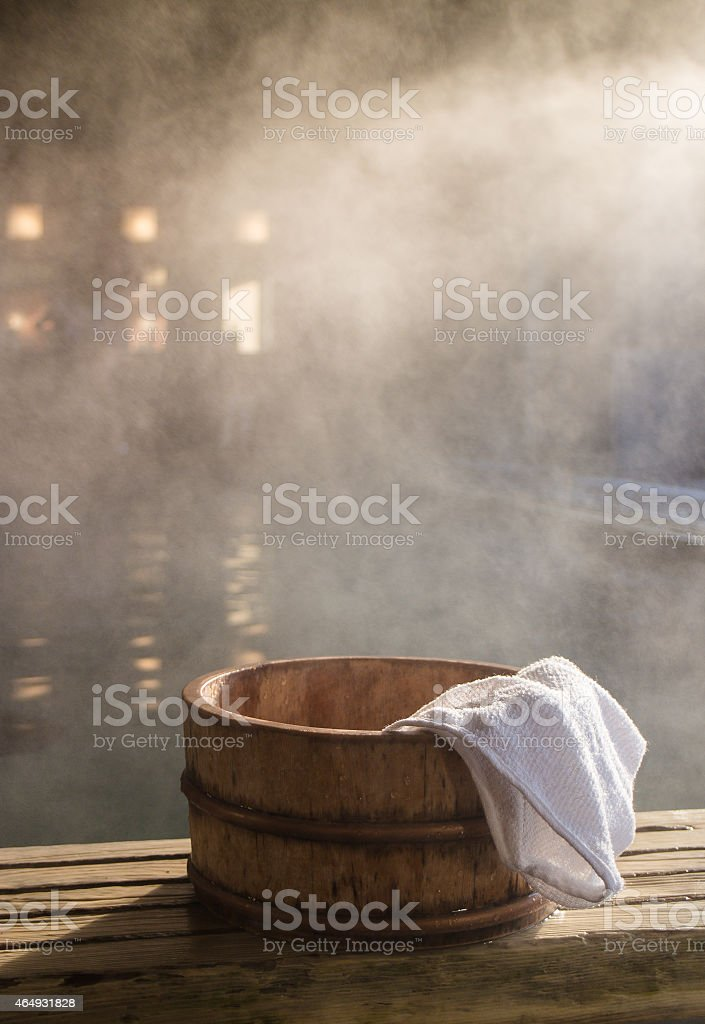 Steamy Onsen with a white towel on the side of a wood barrel stock photo