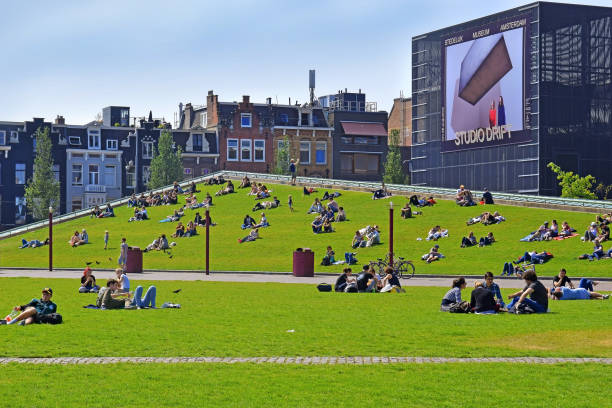 Stedelijk Museum Amsterdam, Netherlands Amsterdam, The Netherlands - May 20, 2018: Amsterdam Stedelijk Museum for modern, contemporary art and design, new wing of the museum and people resting on the lawn of Museumplein museumplein stock pictures, royalty-free photos & images
