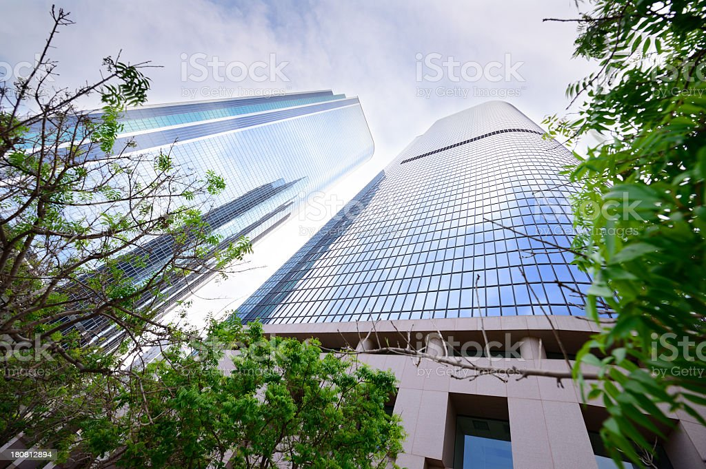 Steel and glass finance building, green trees stock photo