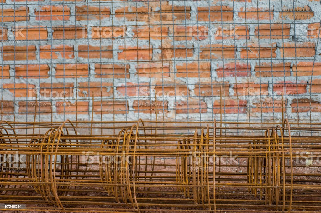 Steel bar have rust put on red soil preparing for building construction with red brick wall. stock photo
