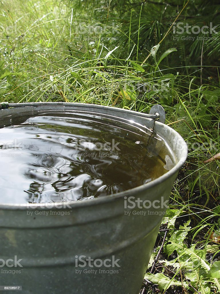 A steel basket full of water in the field stock photo