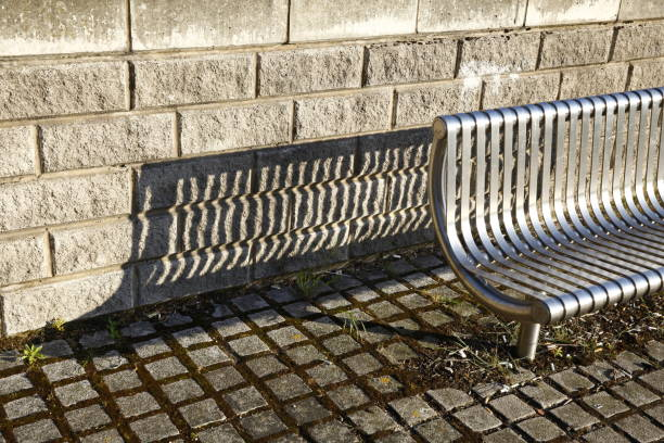 steel bench with long shadow. - doncaster foto e immagini stock