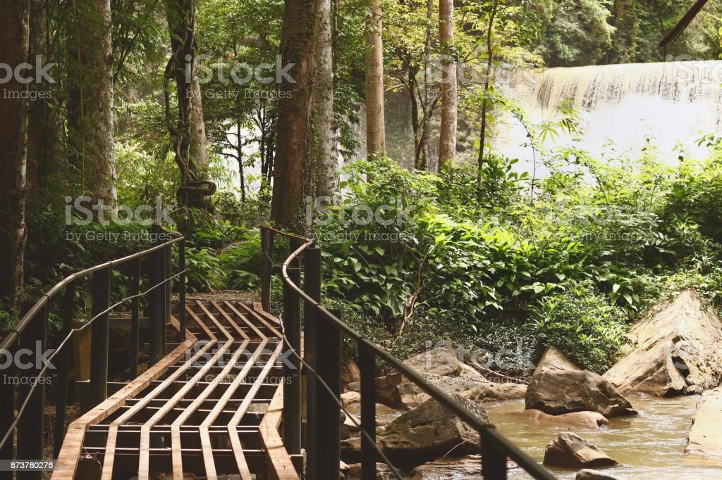 Steel bridge with sridith waterfall in tropical rain forest stock photo