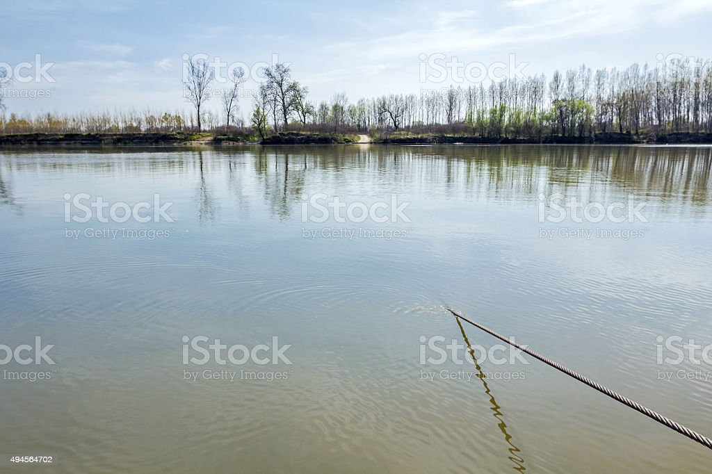 Steel cable oscillating trough water stock photo