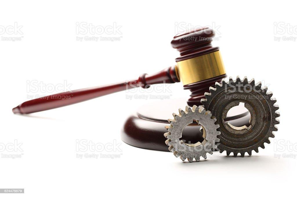 Steel cogwheels on judge's wooden gavel background stock photo