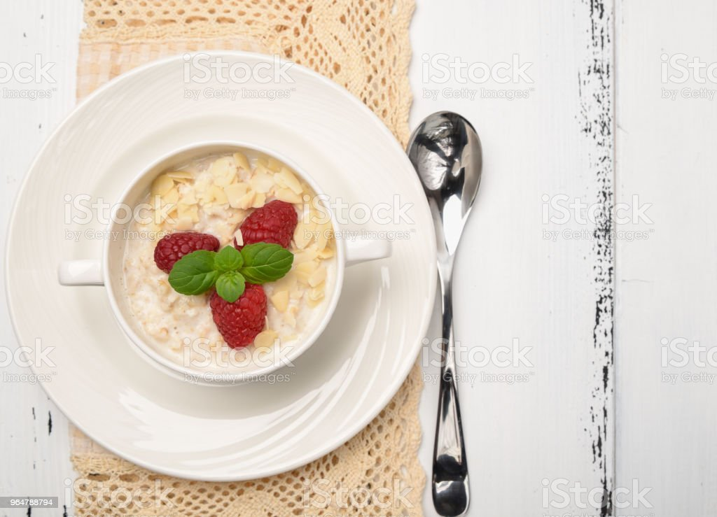 Steel cut oatmeal porridge with raspberry and almond flakes for breakfast royalty-free stock photo
