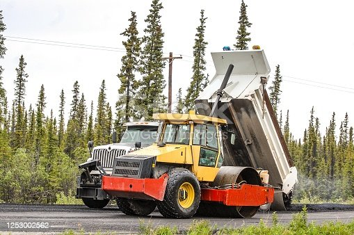 A steel drum roller prepares to smooth out a truckload of hotmix. Time is short in Alaska when it comes to road repair. It won't be long before winter snows blanket the ground again.