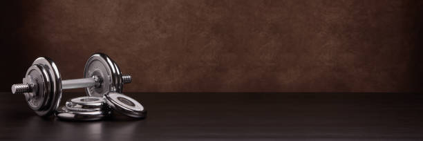 Steel dumbbell and weights on brown background. Fitness, sport, healthy lifestyle concept. Extra wide panorama banner background stock photo