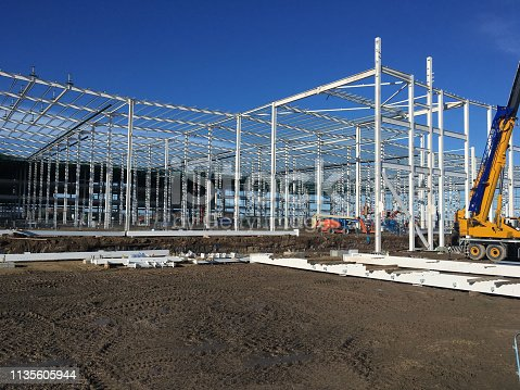 Construction Site with Steel Erection of an Industrial Warehouse and Working at Height Machines