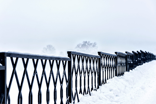 Steel fence along the embankment of the river during the fog in winter in severe frost