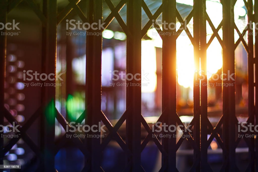 Steel fence and sunset background is represented as protection, imprisonment or deprives stock photo