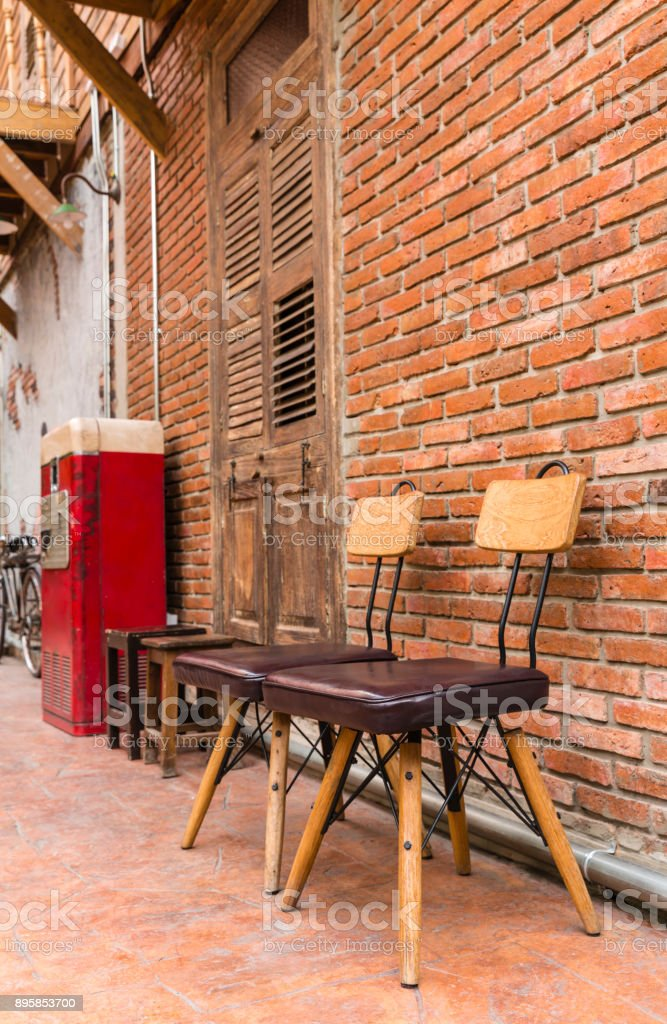 Steel frame chairs are padded with brown cushions and a wooden backrest stock photo