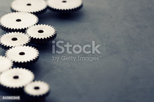 Metal cogs and gears on dark background with copy space.