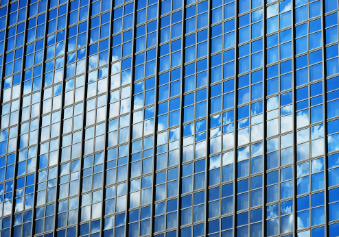 Glass facade reflecting blue sky with white cloudsModern different skyscrapers