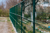 Steel grill. Green fence with wire. Fencing
