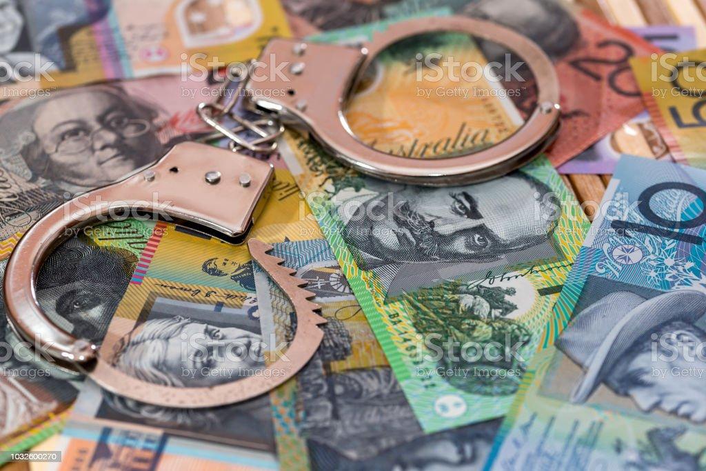 Steel handcuffs on australian dollars background close up stock photo