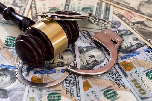 istock Steel handcuffs with judge's gavel on dollar banknotes 1014716240