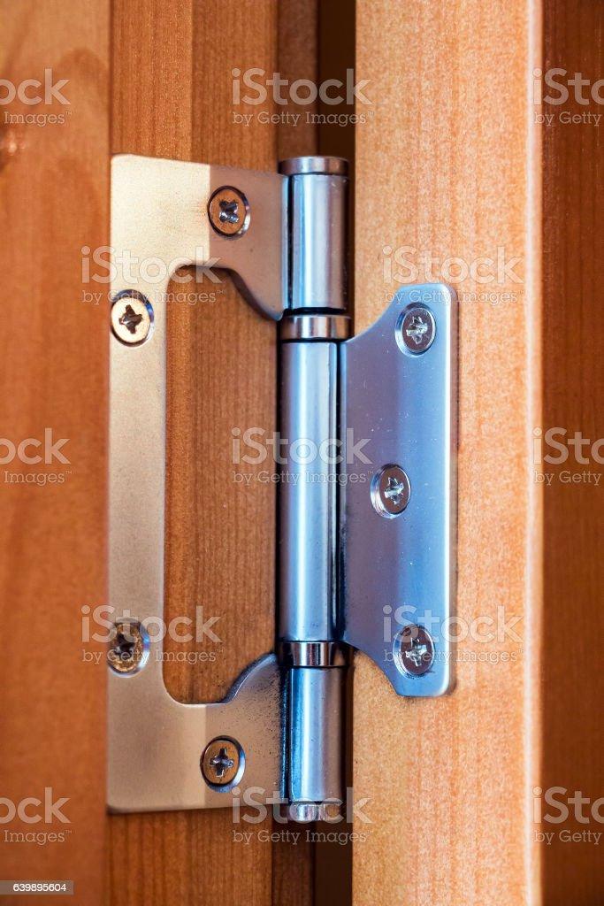 Steel hinge on the wooden door stock photo