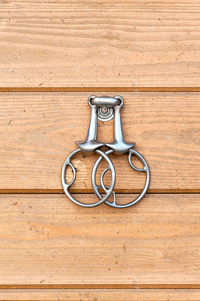 steel horse snaffle-bit hanging on wooden background. - horse bit stock photos and pictures