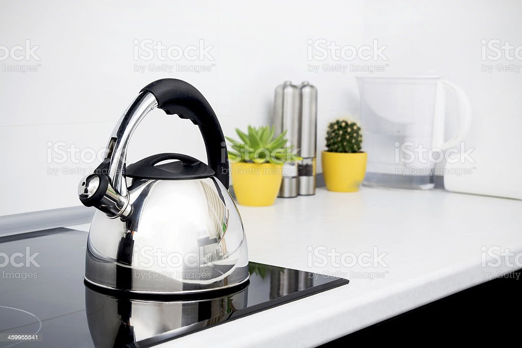 Steel kettle in modern kitchen with induction stove stock photo