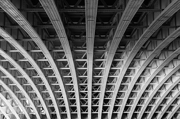 Steel lines under a bridge in London Symmetric steel framework under a bridge over the river Thames in London. arch architectural feature stock pictures, royalty-free photos & images