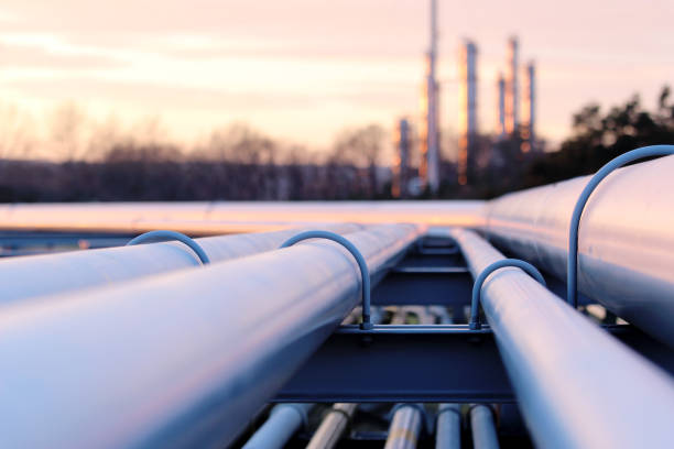 steel long pipes in crude oil factory during sunset - refinery stock photos and pictures