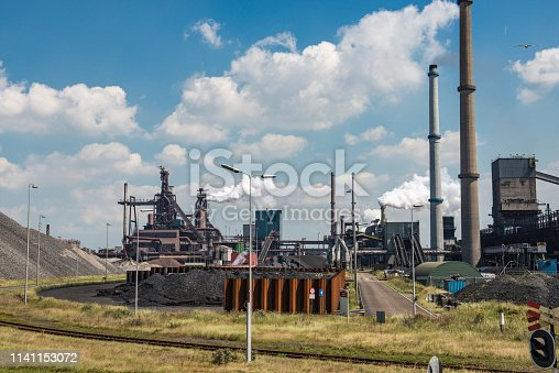 Steel mill with smoking chimneys and heaps of raw material located on the Dutch coast during a cloudy day. Thick smoke is coming from the cimneys.