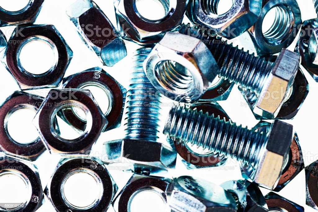 Steel nuts and bolts  shine against white stock photo