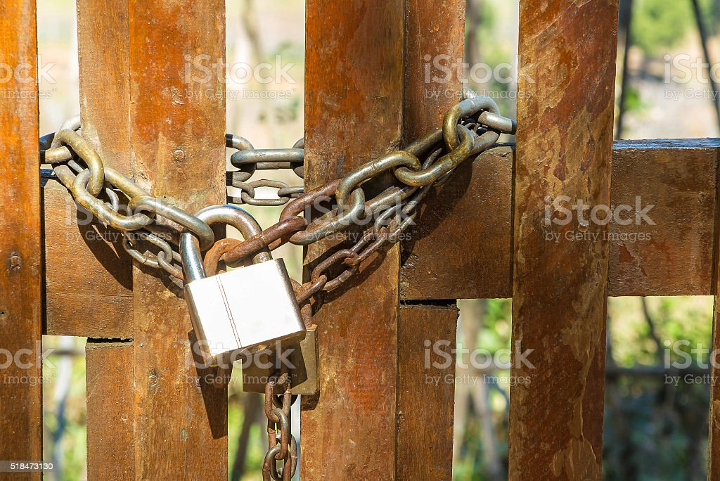 Steel padlock and rusty chain on the wooden door stock photo
