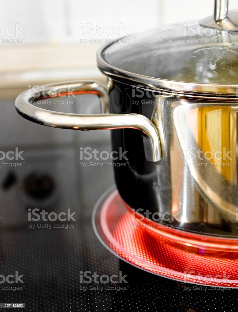 Steel Pot on glowing ceran field stock photo