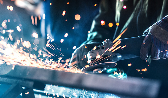 Closeup of unrecognizable men grinding steel at a hardware workshop. There are sparks flying in every direction