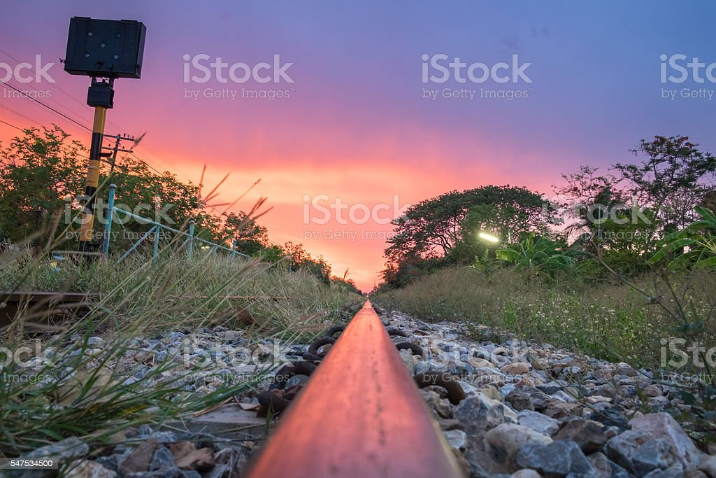 Steel railroad and signpost and twilight sky stock photo