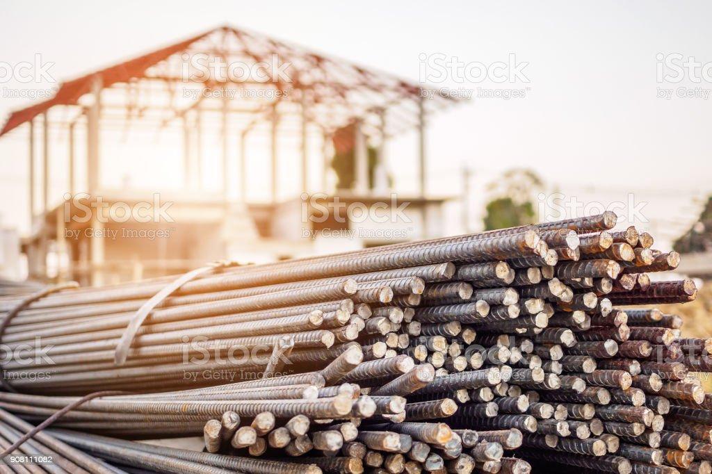 vergalhões de aço para reforço de concreto no local de construção com casa em fundo de construção - foto de acervo