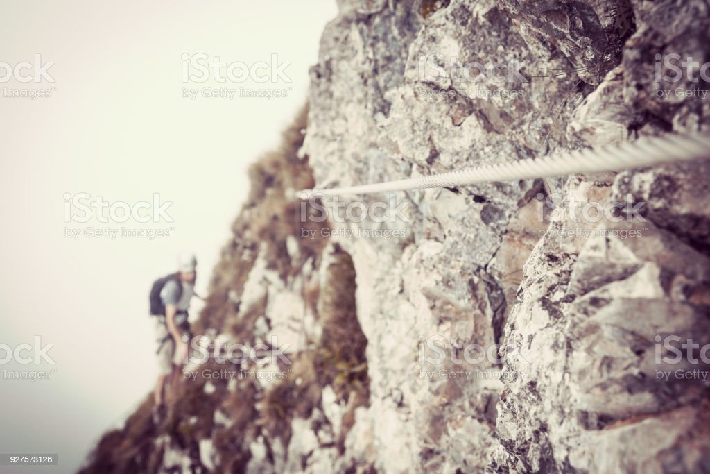 Steel rope on via ferrata with climbers stock photo