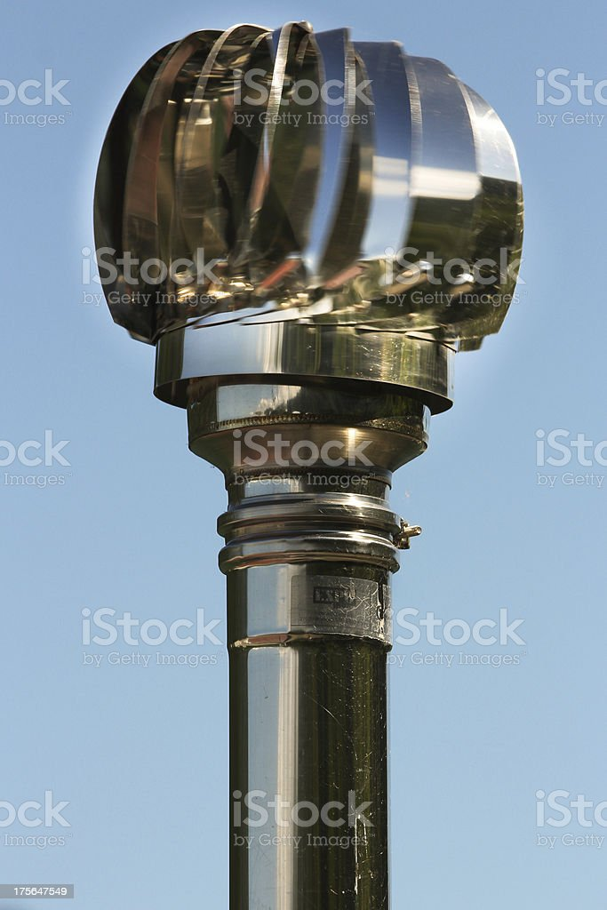 Steel rotor on top of a chimneypot with sky background royalty-free stock photo