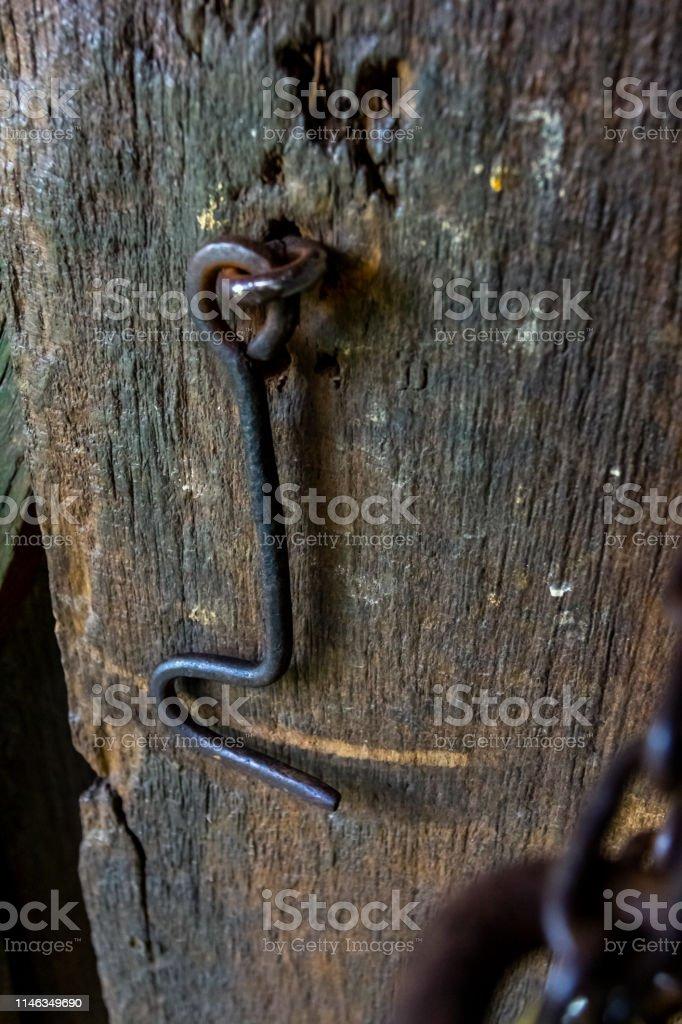 Steel Rusty metal hook on the old wooden door. Iron hook to lock the...