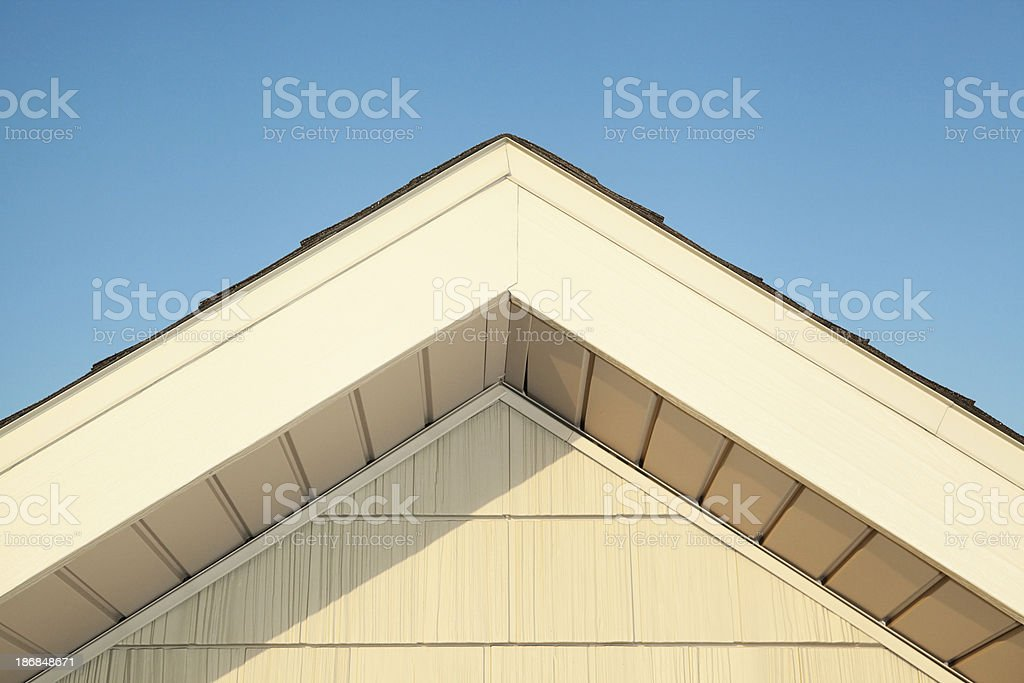 Steel Sided House Roof Peak against Blue Sky stock photo