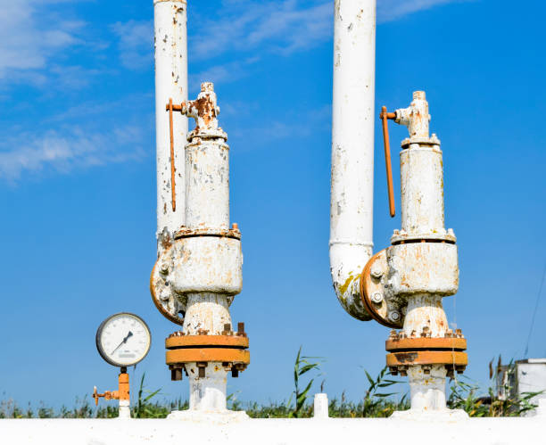 Steel spring safety valve and pressure gauge on the pressure vessel. Oil field equipment. stock photo