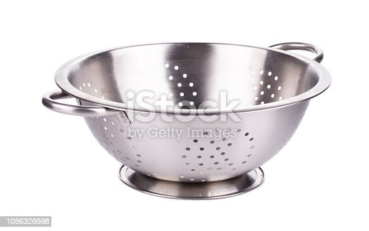 Steel strainer sieve metal bowl. It is isolated in a white background. Close-up.