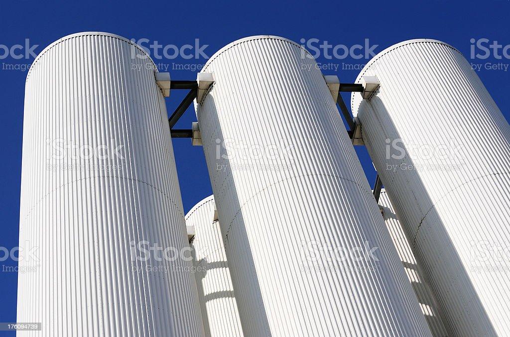 Steel sunlit white silos against dark blue sky royalty-free stock photo