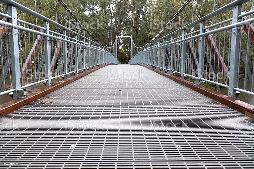 Steel Suspension footbridge over river stock photo