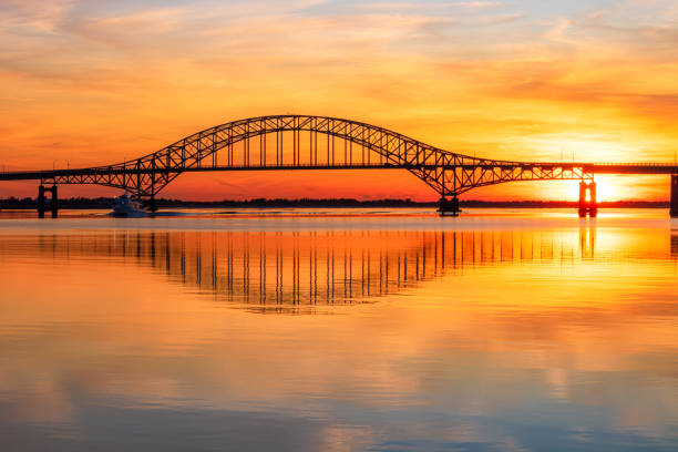 Steel tied arch bridge spanning a bay with crystal clear reflections in the water at sunset.