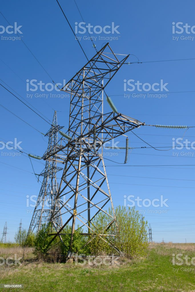 steel towers of a high-voltage power line on a blue sky background - Zbiór zdjęć royalty-free (Amperaż)
