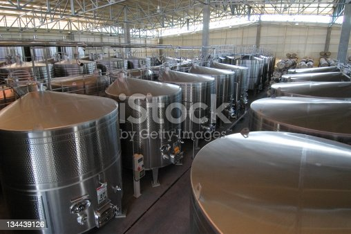 Steel Vats used in Making Wine.  Cylindrical containers holding wine during the fermentation process.  Rows of giant steel containers.  Indoors with skylights allowing natural daylight.