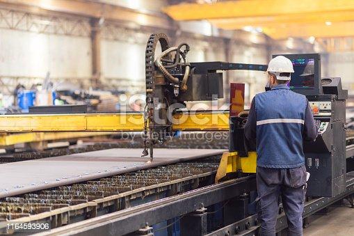 Steel worker on CNC plasma cutter machine