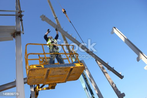 Steel worker on cherry picker. Some motion blur on hands.
