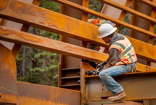 Steel workers puts the finishing fasteners on a bridge across Rubicon Creek, El Dorado National Forest, California.
