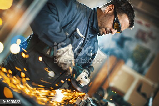 Closeup side view of a worker grinding excess steel on the welded joint between two square steel tubes.
