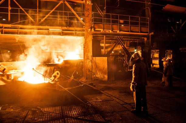 Steelworkers when pouring liquid titanium slag from arc furnace stock photo