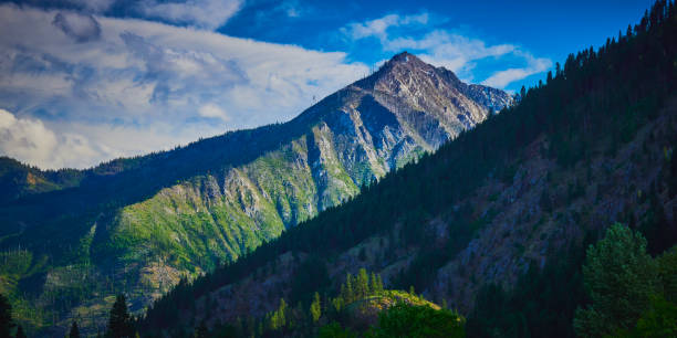 Steep and rugged mountain view in late afternoon with blue sky and wispy clouds near Leavenworth Washington stock photo